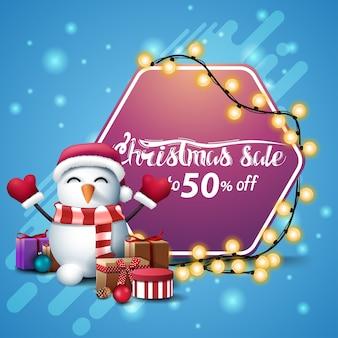 크리스마스 판매, 최대 50 할인, 분홍색 육각형 기호가있는 파란색 사각형 배너가 선물과 함께 산타 클로스 모자에 화환과 눈사람을 감쌌습니다.