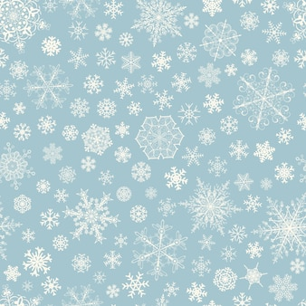 Christmas seamless pattern of big and small snowflakes, white on light blue