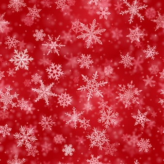 Christmas seamless pattern of complex blurred and clear falling snowflakes in red colors with bokeh effect