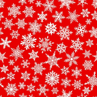 Christmas seamless pattern of complex small snowflakes in white colors on red background