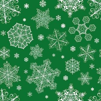 Рождественский фон из больших и маленьких белых снежинок на зеленом фоне