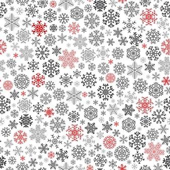 白い背景の上の赤と黒の雪片からのクリスマスのシームレスなパターン