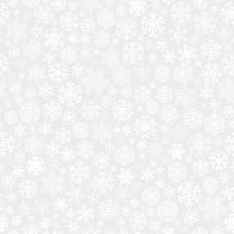 Рождественский фон из белых снежинок на сером фоне