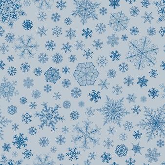 大小の雪片のクリスマスのシームレスなパターン、水色に青