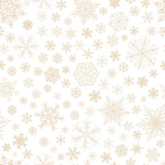 白地に茶色の大小の雪片のクリスマスのシームレスなパターン