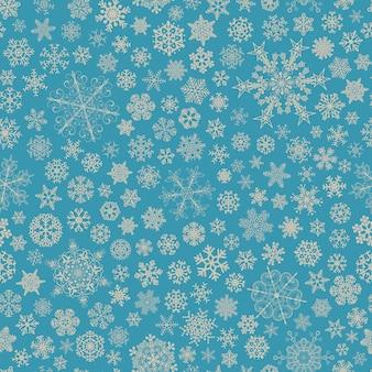 大小の雪片のクリスマスのシームレスなパターン、水色に灰色