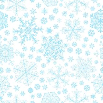 大小の雪片のクリスマスのシームレスなパターン、白地に水色