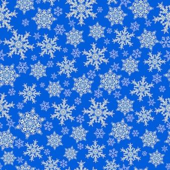 大小の雪片のクリスマスのシームレスなパターン、青に白