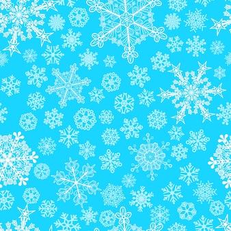 大小の雪片のクリスマスのシームレスなパターン、水色に白