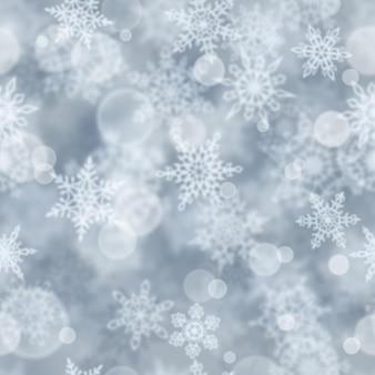 灰色の背景にぼやけた雪片のクリスマスのシームレスなパターン