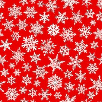赤い背景の上の白い色の複雑な小さな雪のクリスマスのシームレスなパターン