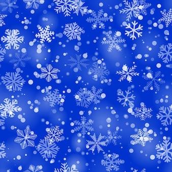 Рождественский фон из снежинок разной формы, размера и прозрачности в голубых тонах