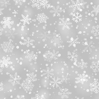 灰色のさまざまな形、サイズ、透明度の雪片のクリスマスのシームレスなパターン