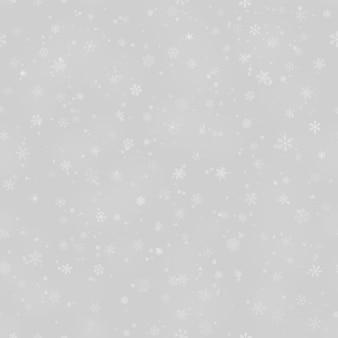 灰色の背景に、さまざまな形、サイズ、透明度の雪片のクリスマスのシームレスなパターン