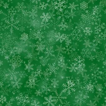 緑の背景に、さまざまな形、サイズ、透明度の雪片のクリスマスのシームレスなパターン