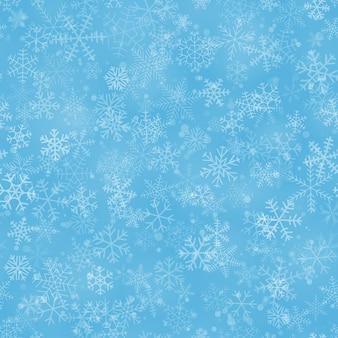 Рождественский фон из снежинок разной формы, размера и прозрачности, на голубом фоне