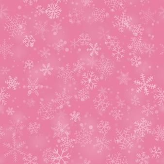 ピンクの背景に、さまざまな形、サイズ、透明度の雪片のクリスマスのシームレスなパターン