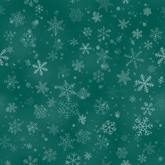 ターコイズブルーの背景に、さまざまな形、サイズ、透明度の雪片のクリスマスのシームレスなパターン