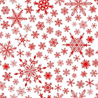 雪片のクリスマスのシームレスなパターン、白地に赤。