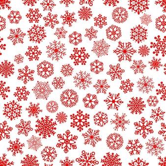 雪片のクリスマスのシームレスなパターン、白地に赤