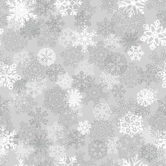 雪片のクリスマスのシームレスなパターン、灰色に白