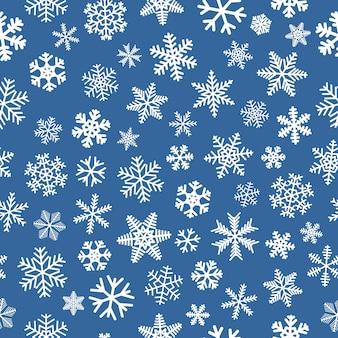 雪片のクリスマスのシームレスなパターン、水色の背景に白