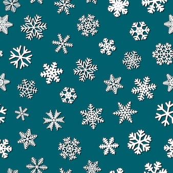 影付きの雪片のクリスマスのシームレスなパターン、青の背景に白