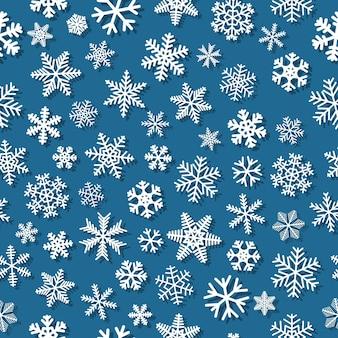影付きの雪片のクリスマスのシームレスなパターン、水色の背景に白