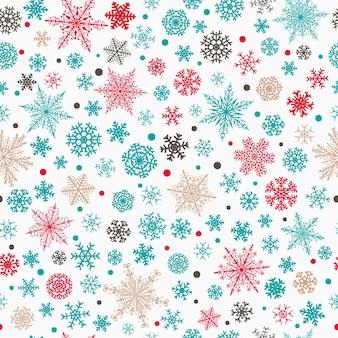 さまざまな複雑な大小の雪片のクリスマスのシームレスなパターン、白い背景の上の多色