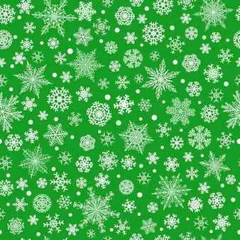 さまざまな複雑な大小の雪片のクリスマスのシームレスなパターン、緑の背景に白