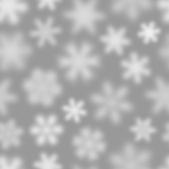 灰色の背景に白いデフォーカス雪片のクリスマスのシームレスなパターン
