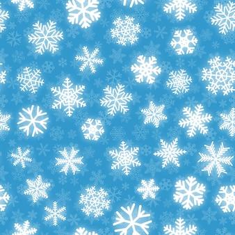 水色の背景にさまざまな形の白い雪のクリスマスのシームレスなパターン