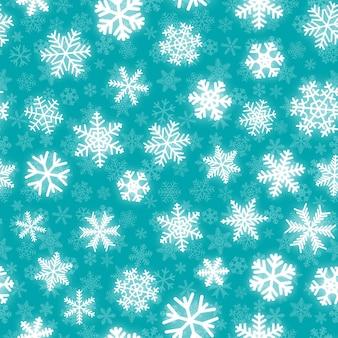 Рождественский фон из белых снежинок разной формы на бирюзовом фоне