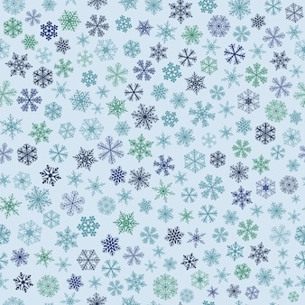 Christmas seamless pattern of small snowflakes, blue and green on light blue