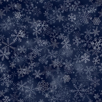 Christmas seamless pattern of snowflakes of different shapes, sizes and transparency, on dark blue background