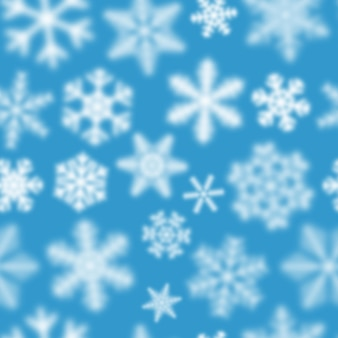 Christmas seamless pattern of white defocused snowflakes on light blue background