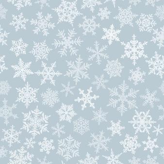 複雑な大小の雪片、灰色の背景に白のクリスマスのシームレスなパターン