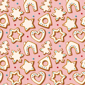 ピンクのニットの背景にジンジャーブレッドクッキーとクリスマスのシームレスなパターン。家とクリスマスツリー、星と雪の結晶とハートの形をした自家製ビスケット。ベクトルイラスト