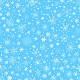 さまざまな複雑な大小の雪片、青の背景に白のクリスマスのシームレスなパターン