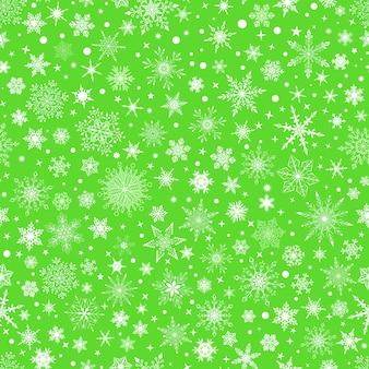 さまざまな複雑な大小の雪片、緑の背景に白のクリスマスのシームレスなパターン