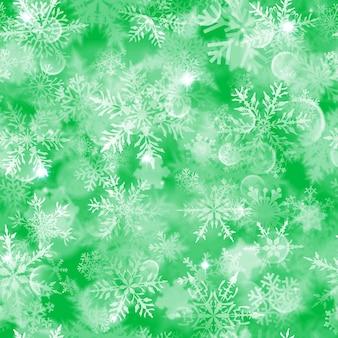 緑の背景に白いぼやけた雪、まぶしさと輝きとクリスマスのシームレスなパターン