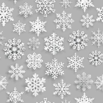 灰色の背景に白い紙の雪片とクリスマスのシームレスなパターン