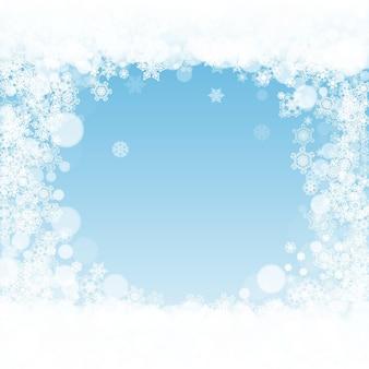 冬の背景にクリスマスの雪。季節の冬のバナー、ギフトクーポン、バウチャー、広告、パーティーイベントのフレーム。クリスマスの雪と青い空。休日のお祝いのために降る雪