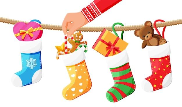 テディベア、ギフトボックス、ジンジャーブレッドマン、キャンディケインとロープのクリスマスの靴下ストッキング。明けましておめでとうございます。休日の新年とクリスマスのお祝い。ベクトルイラストフラットスタイル