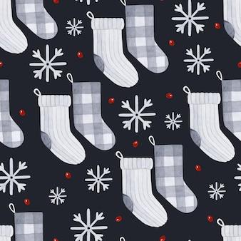暗い背景にクリスマスの靴下と雪片の水彩画のシームレスなパターン Premiumベクター