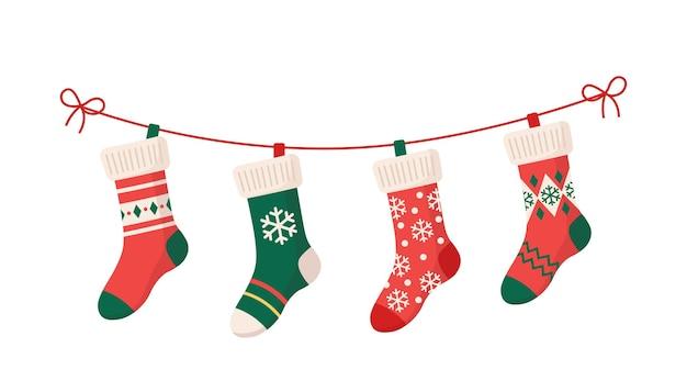 Рождественские чулки с различными традиционными красочными праздничными украшениями. висячие элементы детской одежды с милыми рождественскими узорами на веревке. красные, зеленые носки со снежинками, снеговик, новогодняя елка