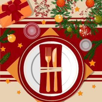 Сервировка рождественского стола. тарелки, золотые столовые приборы, салфетки, стаканы, украшения и декор.