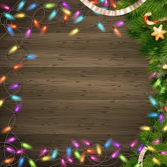 白いウッドの背景のライトとクリスマスツリーブランチ。