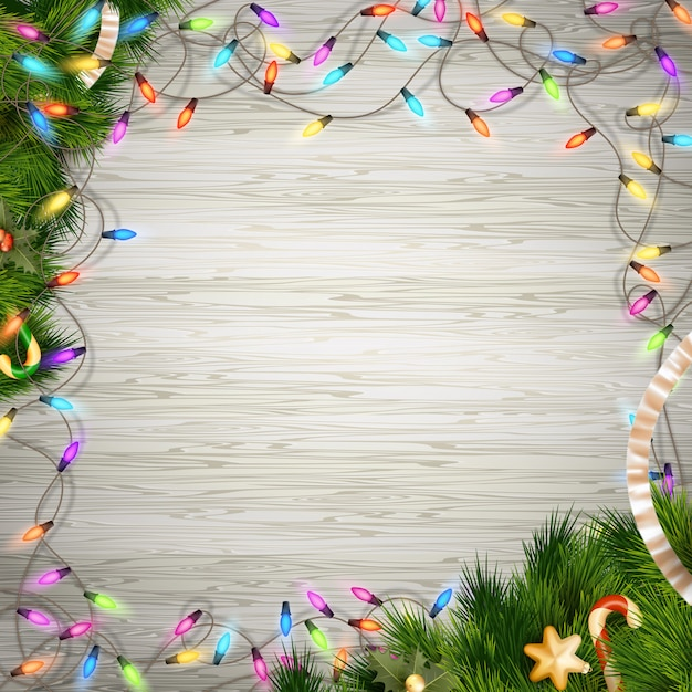 Christmas tree branch with lights on white wood background.