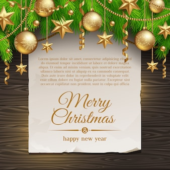 Christmas tree branches with golden decoration and paper banner with holiday greeting.